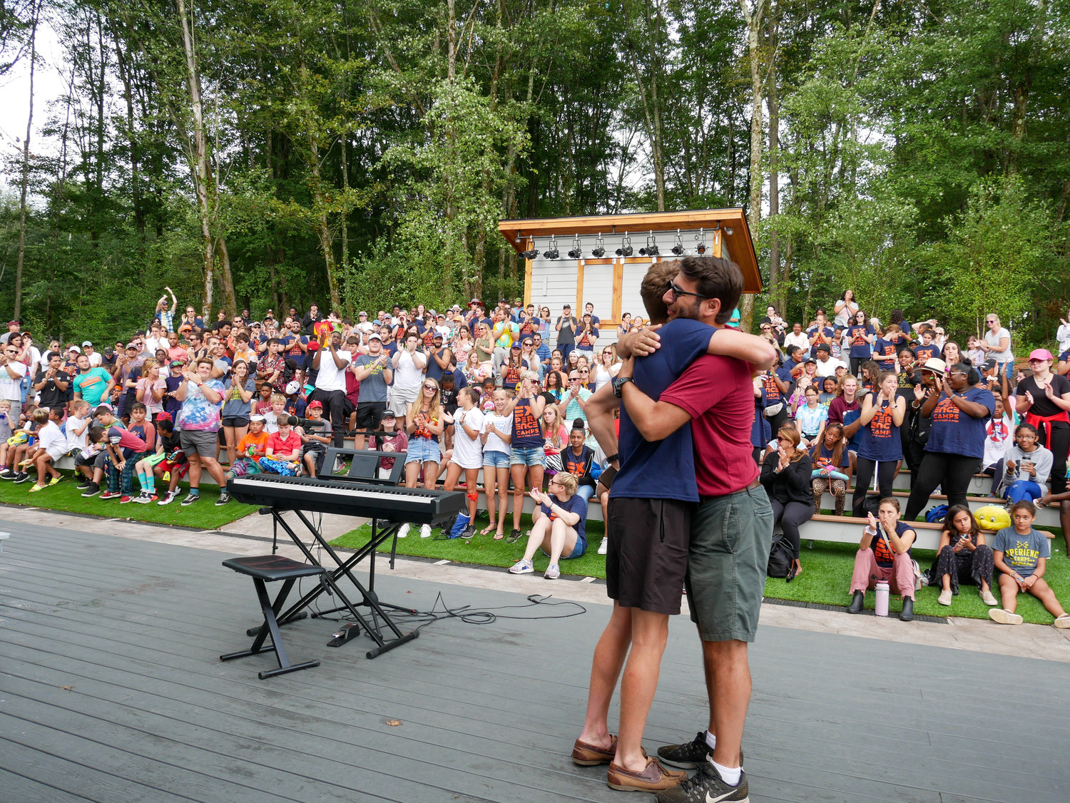 Director and volunteer hugging on stage