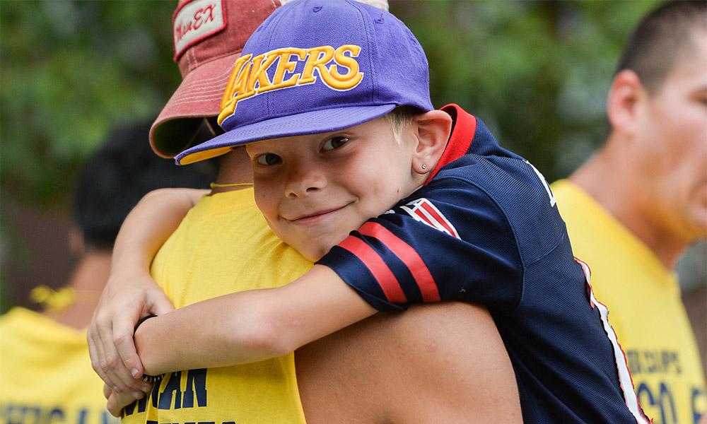 A camper hugging a volunteer