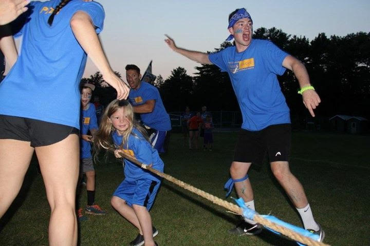 Taylor cheering a kid on doing tug of war